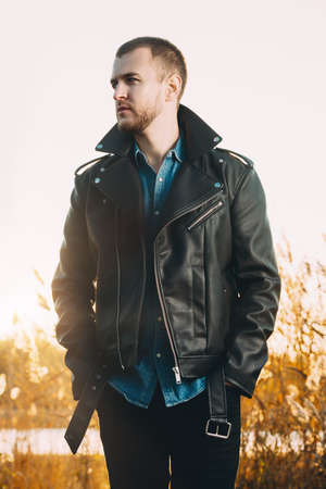 Beau jeune homme en veste en cuir dans le parc de l & # 39 ; automne sur un coucher de soleil. beauté pittoresque Banque d'images - 89094642