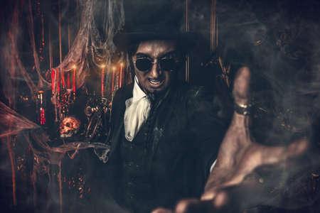 Halloween. Effrayant homme effrayant en noir tend la main. Vieux château abandonné. Le Seigneur des Ténèbres. Un vampire. Banque d'images - 89094675