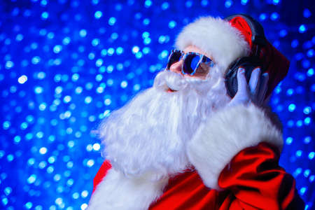 DJ Santa Claus in sunglasses and headphones. Christmas songs and music. Disco lights in the background. Stock Photo