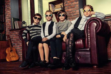 고급스러운 아파트에 선글라스와 학교 유니폼을 입고 포즈를 취하는 현대 어린이의 그룹입니다. 학교 패션.