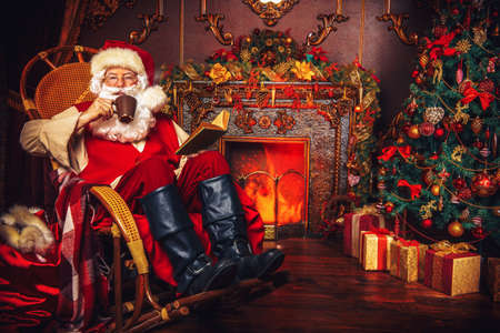 Il buon vecchio Babbo Natale che ha un resto nella sua casa accanto al camino e albero di Natale. Archivio Fotografico - 89098902