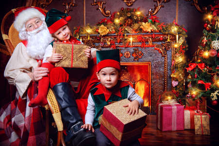 サンタ クロース、ギフト用の箱とエルフの子供。クリスマスの奇跡。