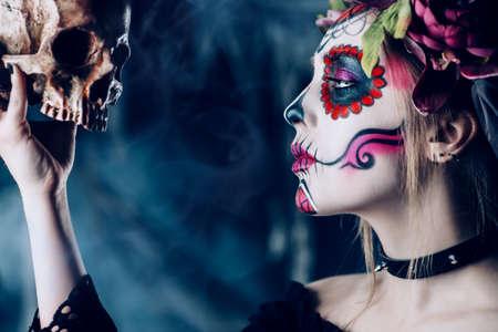 Calavera Catrina in black dress holding a skull over dark scary background. Sugar skull makeup. Dia de los muertos. Day of The Dead. Halloween.   Standard-Bild