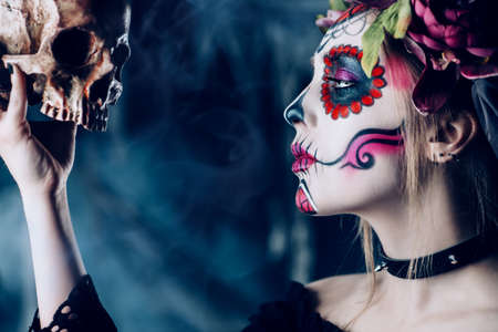 Calavera Catrina in black dress holding a skull over dark scary background. Sugar skull makeup. Dia de los muertos. Day of The Dead. Halloween.   Archivio Fotografico