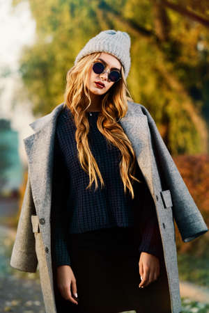 Seasonal autumn fashion. Modern young woman wearing fashionable warm clothes posing in the autumn park. Stock Photo