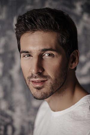 白い t シャツを着ているハンサムな若い男の肖像画。スタジオ撮影します。男性の美と健康。