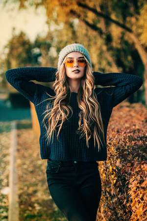 Modern young woman wearing warm clothes posing in the autumn park. Autumn fashion. Reklamní fotografie - 89197349
