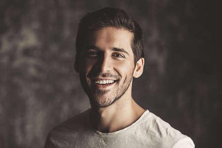 흰색 t- 셔츠를 입고 잘 생긴 웃는 젊은 남자의 초상화. 스튜디오 어두운 배경 위에 쐈어. 남성의 아름다움과 건강. 스톡 콘텐츠