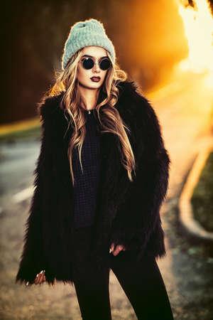 가을 패션 쐈어. 유행 젊은여자가 따뜻한 옷을에 일몰에 고속도로 포즈. 청소년 스타일. 스톡 콘텐츠