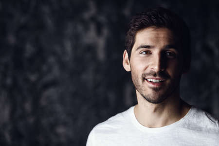 Portrait of a handsome smiling young man wearing white t-shirt. Studio shot over dark background. Mens beauty and health. Stock Photo
