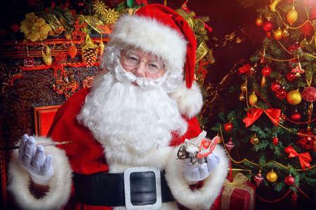 Workshop of Santa Claus. Close-up portrait of Santa Claus making Christmas gifts at home.
