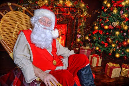 Santa Claus in his house next to the fireplace and Christmas tree resting in armchair. Stock Photo