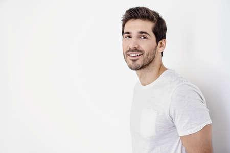 Glücklicher junger Mann, der Kamera und das Lächeln betrachtet. Die Schönheit und Gesundheit von Männern.