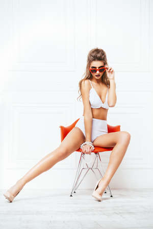 Sexual young woman in a beautiful white lingerie and  sunglasses. Fashion shot.