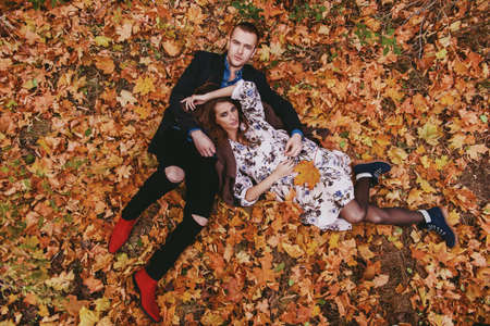 Autumn fashion. Beautiful fashionable couple lying on yellowed autumn grass and leaves.
