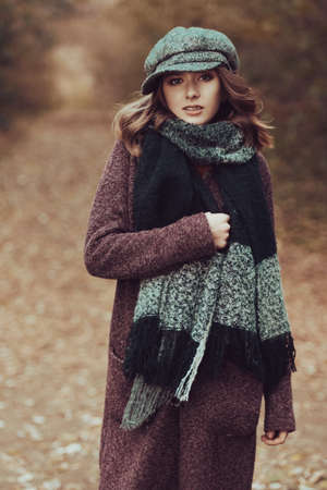 Nettes jugendlich Mädchen in der modernen Kleidungsaufstellung im Freien. Warmer Herbsttag. Saisonale Herbst- und Wintermode. Standard-Bild - 89336509