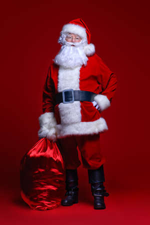 Christmas and New Year concept. Santa Claus comes with big bag of gifts. Full length portrait over red background.