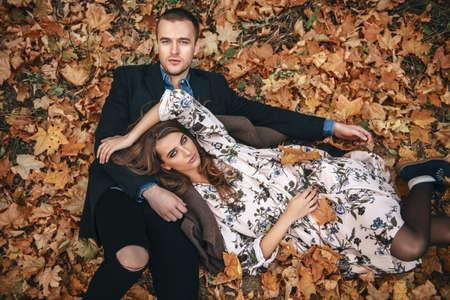 秋のファッション。黄色の秋の草と葉の上に横たわっている美しいファッショナブルなカップル。 写真素材