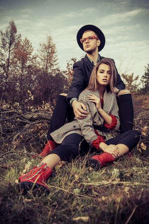 秋のファッション。黄ばんだ秋の草や葉の美しいファッショナブルなカップル。