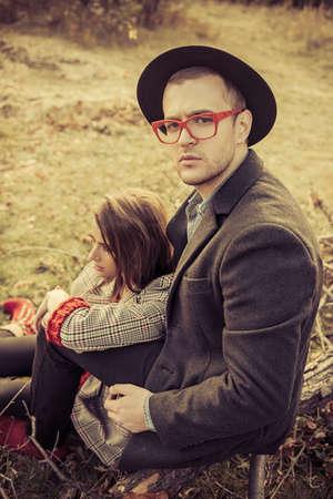 秋のファッション。黄色の秋の草と葉の上に美しいファッショナブルなカップル。
