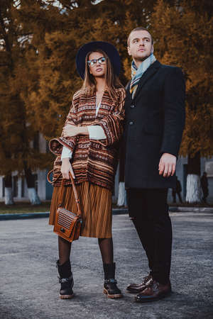 Full length portrait of a beautiful young people walking in the autumn park. Autumn fashion.