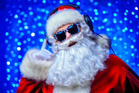 DJ Santa Claus in sunglasses and headphones. Christmas songs and music. Disco lights in the background. Stock fotó