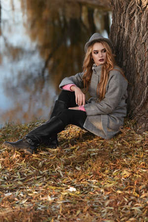 Romantic young woman is sitting under the tree in a beautiful autumn park. Beauty, Autumn fashion. Stock Photo