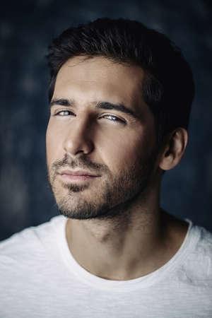 ホワイト t シャツを着たハンサムな青年のクローズアップポートレート。スタジオショット。男性の美しさと健康。
