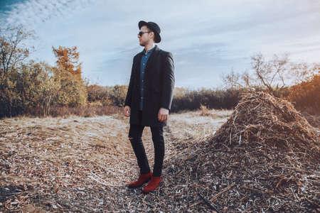가을 패션. 검은 코트, 모자와 선글라스 야외 포즈 잘 생긴 남자 모델. 가 자연입니다.