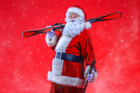 Portrait of Santa Claus holding skiing. Christmas holidays and winter activities.