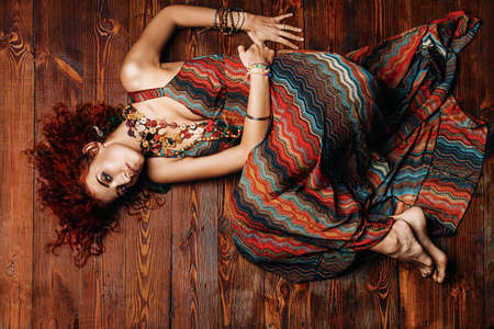 Beautiful bright woman with curly foxy hair wears a dress and beads in boho style. Ethnic style in clothes. Фото со стока