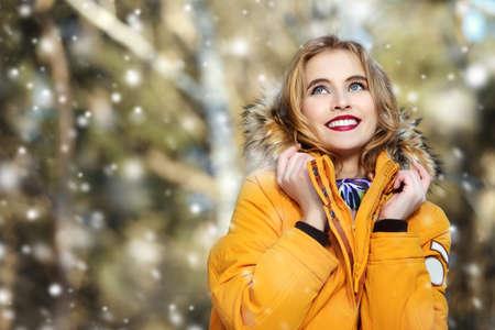 Mädchen, das in Wald am Wintertag geht. Mode erschossen. Daunenjacken.