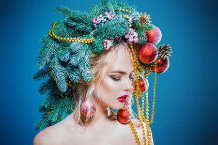 Portrait of a beautiful young woman with christmas tree in hairstyle decorated with beads and balls. Holiday make-up. Beauty, fashion. Foto de archivo