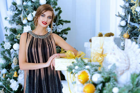 Merry Christmas and Happy New Year. Pretty young woman in evening dress poses near the Christmas tree. Beauty, fashion. Make-up, cosmetics.