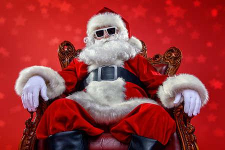 Koele moderne kerstman in zonnebril op rode achtergrond. Kerst concept.