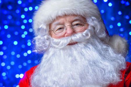 Christmas concept. Close-up portrait of a fairytale Santa Claus. Good old traditions. Family holidays. Holiday lights in the background.