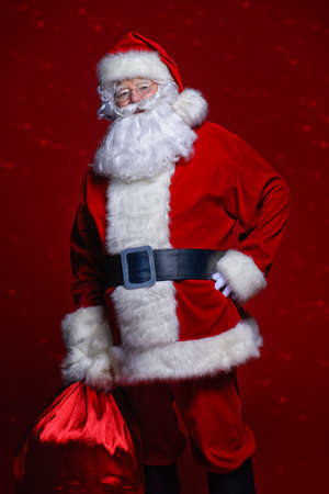 Christmas concept. Portrait of a fairytale Santa Claus over red background. Good old traditions. Family holidays. Stock Photo