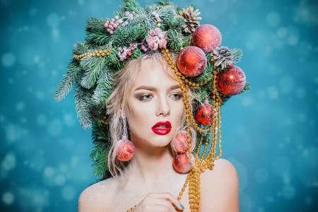 髪型でクリスマス ツリーを持つ美しい若い女性の肖像画は、青い背景にビーズとボールが装飾されています。休日メイク。美容、ファッション。