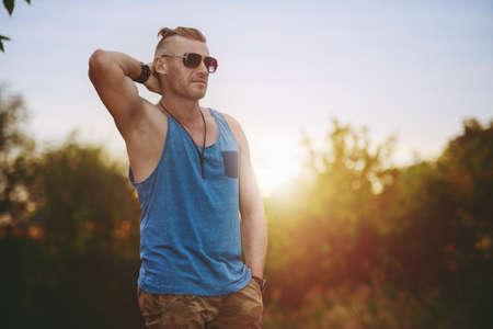 Porträt eines männlichen gutaussehenden Mannes in der zufälligen Kleidung, die im Freien steht. Männermode.