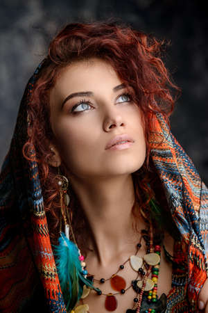 Close-up portrait of a beautiful red-haired woman wears a kerchief, earrings and beads in boho style. Ethnic style in accessories.