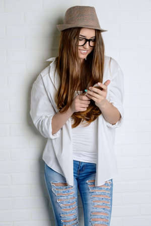 Pretty young woman wearing white shirt and jeans uses her smartphone. Happy lifestyle. Beauty and youth concept. 版權商用圖片