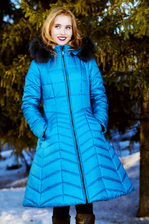 Girl walking in forest on winter day. Fashion shot. Down Jackets. Stockfoto