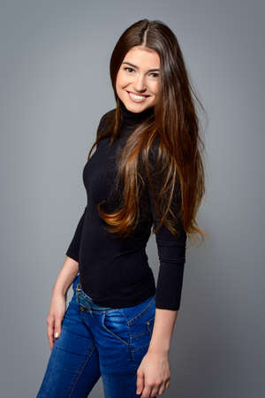 Portrait of a happy young woman with beautiful smile. Long hair concept. Hairstyle, healthy hair. Cosmetics and make-up. 스톡 콘텐츠