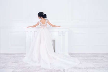 Full length portrait of a beautiful bride woman look from the back in elegant pale apricot wedding dress. Luxurious apartments. Stock Photo