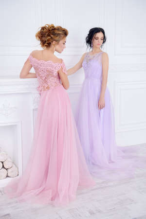 Two beautiful ladies in elegant evening dresses stand in white luxurious apartments. Beauty, fashion. Wedding style.  免版税图像