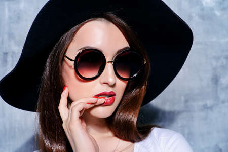Close-up portrait of a hipster girl wearing hat and round sunglasses. Beauty, cosmetics. Banco de Imagens