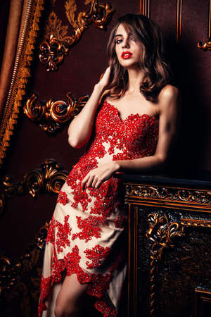Sexual young woman in red dress in a luxury apartment. Classic vintage interior. Beauty, fashion. Evening makeup and hairstyle. Stock Photo