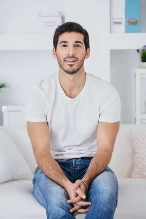 Positive young man wearing white t-shirt and jeans looking at camera and smiling. Men's beauty and health.