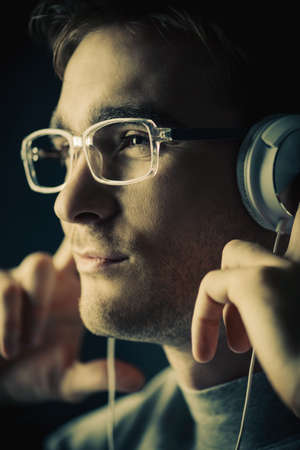 Handsome young man listenig to music in headphones and smiling. Stock Photo