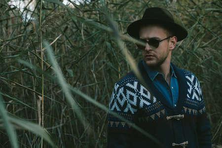 Mode d'automne. Portrait d'un bel homme portant cardigan et chapeau debout en plein air sur fond de nature automne. Banque d'images - 90770336